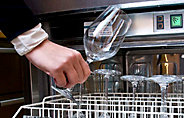 Man takes freshly washed glass from dishwasher