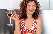 Woman with auburn hair holding red wine glass in right hand